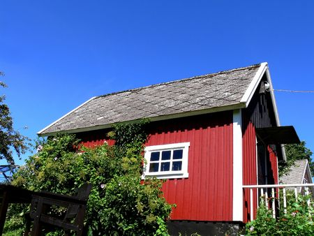 A small red classic wooden house on the countryside in soutern Sweden