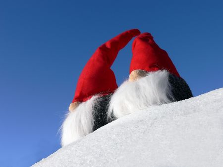 Two bearded santas on a snowy slope under a bright blue sky