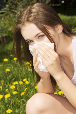 Young woman with allergy during sunny day is wiping her nose. photo