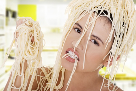 Young beautiful woman with spaghetti noodles on her hairs photo