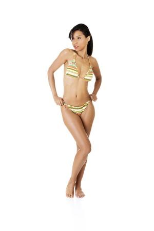 Full portrait of dark skined girl in bikini, isolated on white photo