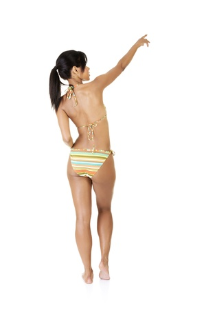Happy excited tanned summer woman pointing on copy space. Isolated on white. photo