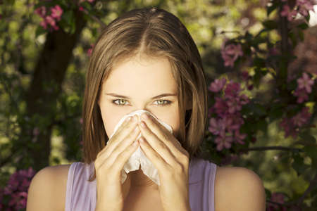 during the day: Young woman with allergy during sunny day is wiping her nose.