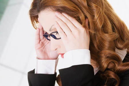 holding the head: Businesswoman with a headache holding head