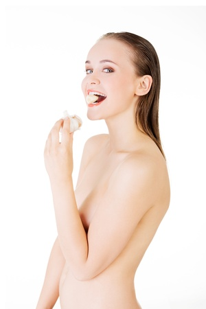 Young beautiful woman eating garlic. Healthy eating concept. Natural antibiotic that fight infection  photo
