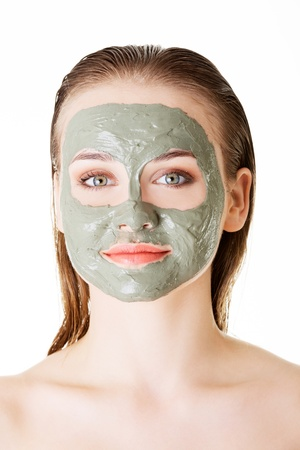 Beautiful woman with green clay facial mask, isolated on white  Stock Photo - 22466089