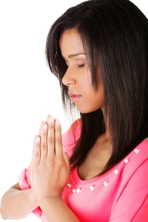 african worship: Young pretty woman praying, over white background.
