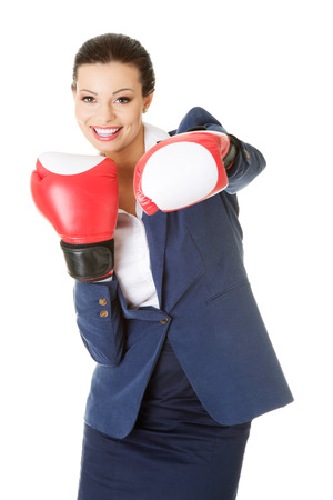 Young businesswoman with boxing gloves, isolated on white background  photo