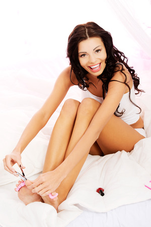 seperator: Attractive woman cutting her nails in bed.