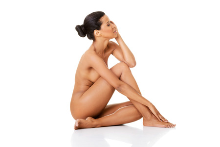 african american nude: Sexy fit naked woman with healthy clean skin sitting, isolated on white background  Stock Photo