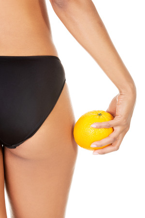 A girl holding an orange next to the buttocks, isolated on white  photo