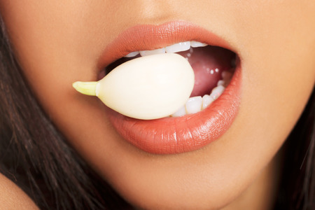antibiotic: Young beautiful woman eating garlic. Healthy eating concept. Natural antibiotic that fight infection