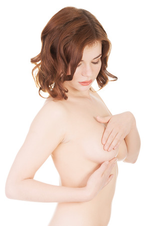 Young Caucasian adult woman examining her breast for lumps or signs of breast cancer  photo