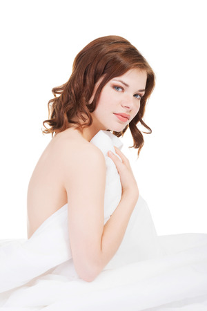 Young beautiful girl woke up and sitting on a bed. White background. photo