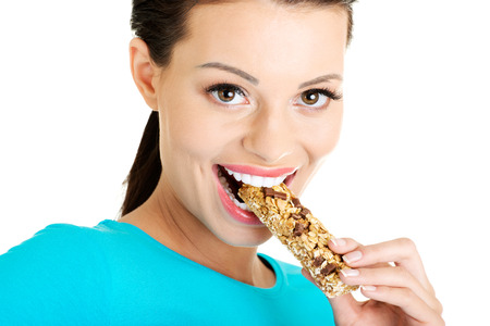 roughage: Young woman eating Cereal candy bar, isolated on white