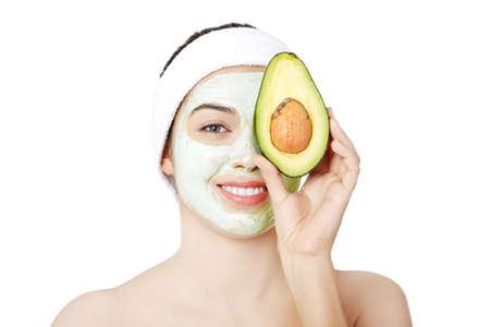 avocado: Giovane donna con un sorriso in possesso di avocado ansante maschera di argilla viso sul viso in un centro termale Archivio Fotografico