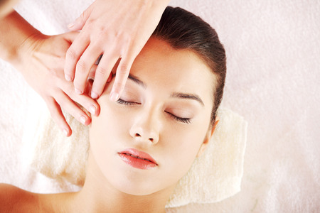 tratamiento facial: Hermosa mujer joven disfrutar de un masaje relajante recibe rostro en el spa