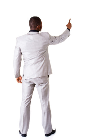 Young businessman pointing on copy space. back view. Isolated on white.  photo