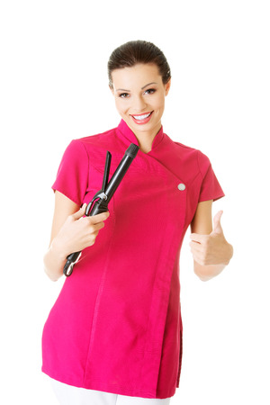 Attractive beautiful womanbeautician holding hair straightener, showing OK. Isolated on white.  photo