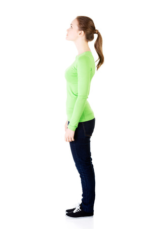 Attractive woman standing and looking up. Side view. Isolated on white.  photo