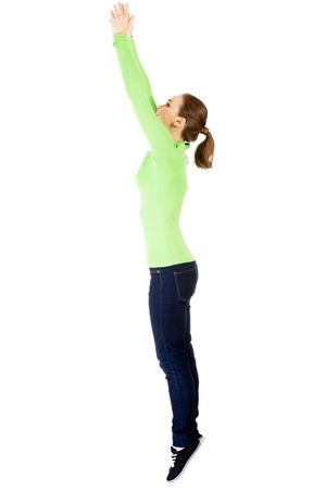 strenghten: Attractive young woman jumping. Side view. Isolated on white.