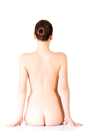 nudity young: Naked woman sitting. Back view. Isolated on white.