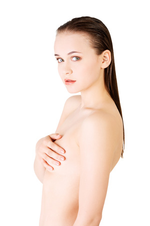 Attractive woman holding her breasts. Side view. Isolated on white.  photo