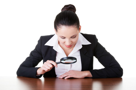 Business woman looking through magnifying glass on table. Isolated on white.  photo