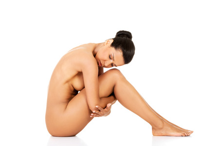 Attractive naked woman sitting. Side view. Isolated on white.  photo