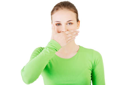 hands in mouth: Attractive woman covering her mouth.  Isolated on white.  Stock Photo