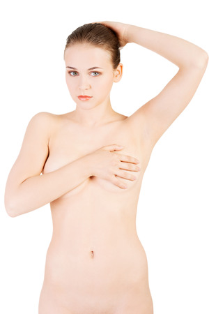Sexy naked woman holding her breasts and holding arm behind the neck. Isolated on white.  photo