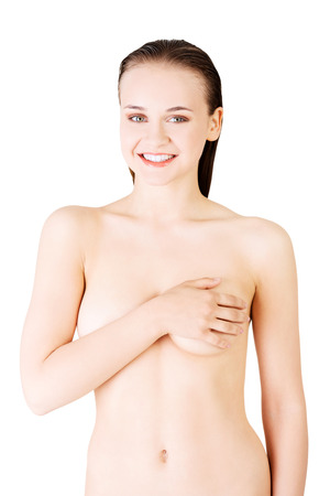 Attractive young woman holding breast. Front view. Isolated on white.  photo