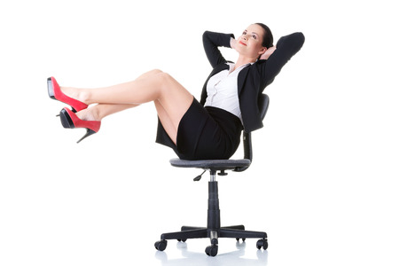 business woman legs: Business woman sitting on a chair with legs up. Isolated on white.  Stock Photo