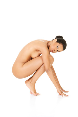 Beautiful naked woman in a crouch, holding her knees. photo