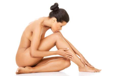 nackt: Attraktive nackte Frau sitzt. Seitenansicht. Isoliert auf Zeit.
