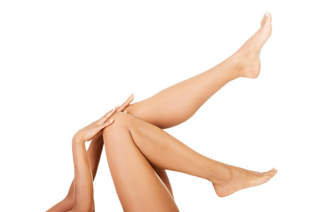 Attractive naked female's leg up. Isolated on white.  photo