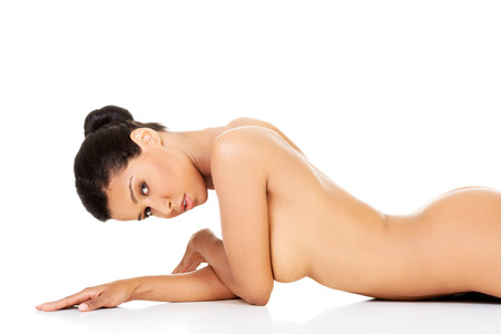 Attractive naked woman lying on the floor on her belly. Side view. Isolated on white.  photo