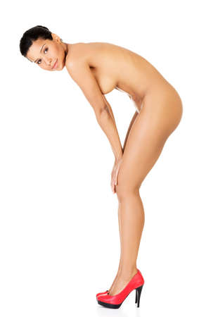 Naked woman in red high heels. Side view. Isolated on white.