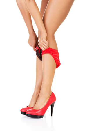 Attractive legs in high heels with red panties. Isolated on white.  photo