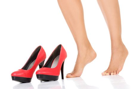 Female legs and red heels. Isolated on white.  photo