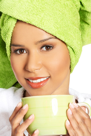 Attractive woman wrapped in towel with turban on head, holding a cup. isolated on white.  photo