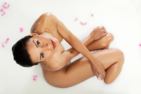 Attractive naked woman lying in a milk-bath. Up front view. photo