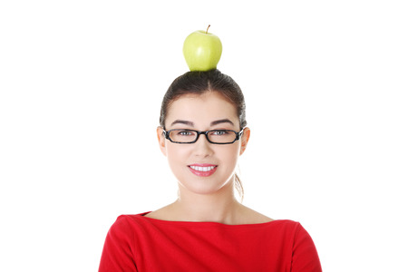 Portrait of attractive young woman with apple on head. Isolated on white.  photo