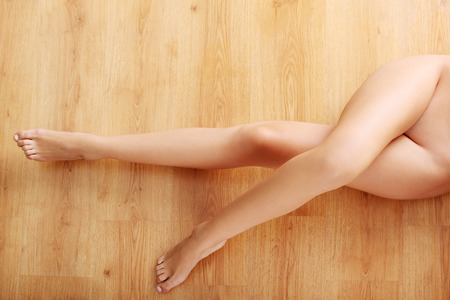Beautiful naked body lying on the floor. Wooden background. photo