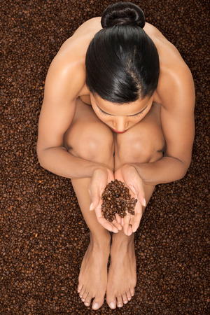 Beautiful naked woman sitting in coffee seeds holding them on hands. Up front view. Closeup.  photo