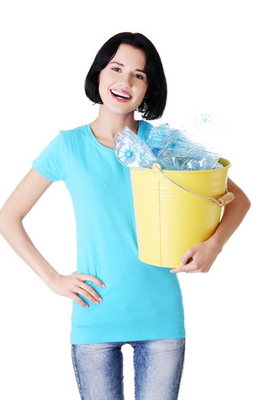 Attractive woman holding bin with plastic bottles. Recycling. isolated on white.  photo