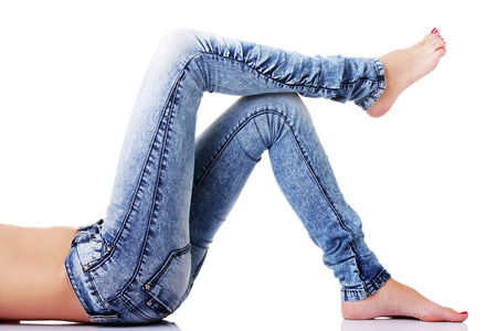 Female's legs in jeans on the floor. Side view. isolated on white.  photo