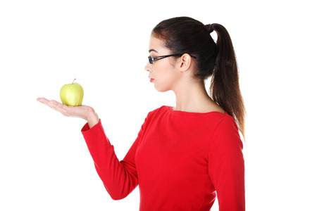 Attractive woman in eyeglasses with apple on hand. Isolated on white.  photo