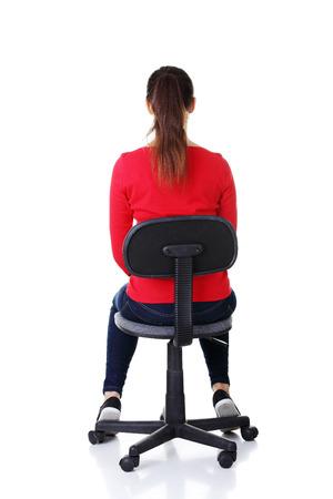 donna seduta sedia: Felice casual donna seduta su una sedia. Vista posteriore. Isolati su bianco. Archivio Fotografico