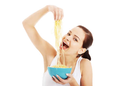 Beautiful woman eating pasta from a bowl  Isolated on white   photo